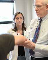 Dr Dale Stafford and medical student anna quinlan examine patient for use in deans newsletter