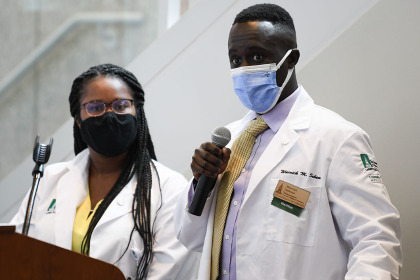 Mialovena Exume and Warrick Sahene stand at a podium in Hoehl Gallery wearing their medical student white coats and cloth face masks